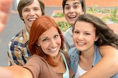 Group of student teenage friends taking selfie laughing at camera