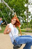 Two teenagers sitting swing in park playground laughing having fun