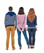 Back view of three people. beautiful friendly girl and guy together. Rear view. Isolated over white