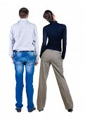Back view of two young business people hug and look into the distance. Rear view. Isolated over whit
