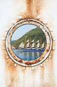 Big Sailing Ship Behind Round Rusted Porthole On White Wall