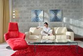 Young woman at home relaxing in her lliving room reading a digital tablet PC surf internet and work