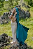 fashionable beautiful woman with blue cloak posing outdoor