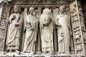 PARIS, FRANCE - NOV 05, 2012: Emperor Constantine, angel, St Denis holding his head, and angel, detail of Notre Dame cathedral. The Portal of the Virgin, dedicated to the patroness of the cathedral.