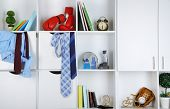Beautiful white drawers and shelves with different home related objects. Male room concept