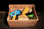 Wooden box with different tools, on wooden table, on dark background