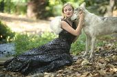 Beautiful Woman Posing With a Wolf Outdoors