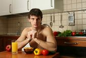 Young muscular man eating his breakfast at the kitchen