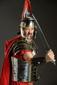 Portrait of Roman Centurion brandishing sword over neutral background