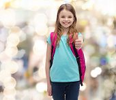 education, gesture and school concept - happy and smiling little girl with school bag showing thumbs