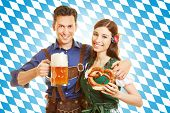 Happy couple at Oktoberfest with beer and pretzel in front of bavarian flag