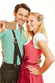Happy couple taking selfie with smartphone in Bavaria