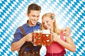 Happy couple drinking beer at Oktoberfest in Bavaria