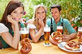 Happy friends sitting in beer garden in Bavaria with pretzel