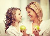 picture of mother and daughter with green apples