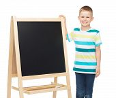 people, advertisement, childhood and education concept - happy little boy with blank blackboard