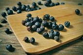 a pile of juniper berries on a rustic wooden table