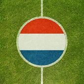 Football field center closeup with Dutch flag in circle
