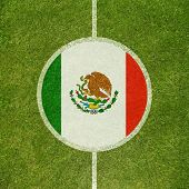 Football field center closeup with Mexican flag in circle