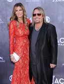 LOS ANGELES - APR 06:  Vince Neil & Lia Gerardini arrives to the 49th Annual Academy of Country Musi