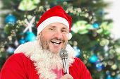 stock photo of christmas song  - Cheerful mature fat man in Santa Claus costume singing Christmas songs with microphone - JPG