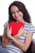 Portrait of a charming young girl on a white background holding a heart