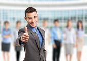 Smiling businessman giving thumbs up in front of his team