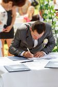 Groom Signing Certificate In Park