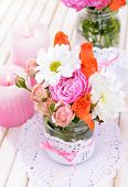 Beautiful bouquet of bright flowers in jars on table close-up
