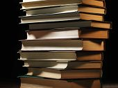 Pile of hardcover books stacked on top of one another in a shadowy room on a wooden desk with copysp