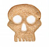 stock photo of dangerous  - Skull shaped piece of bread cut from whole wheat loaf to illustrate danger from gluten in wheat products - JPG