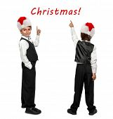 little boy in a tuxedo and  in Santa Claus xmas red hat pointing at wall. Rear view.