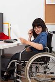 Disabled Young Girl On Wheelchair Working In Her Office