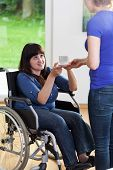 Female Caregiver Giving Cup Of Tea To Woman On Wheelchair