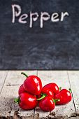 red hot peppers and blackboard on rustic wooden table