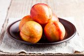 fresh nectarines in a plate on a wooden board