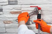 image of adjustable-spanner  - Plumber in orange gloves  mounting a flexible pipe to a valve with adjustable spanner monkey wrench from behind on grey stone wall - JPG