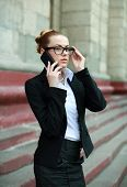 Young Business Woman In Black Suit And Glasses Talking On The Phone Outdoors