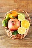 Ripe citrus with green leaves in basket on wooden background