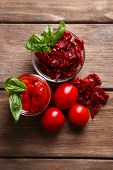 Sun dried tomatoes in glass jar, basil leaves on wooden background