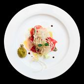 Tuna carpaccio on plate isolated over black background