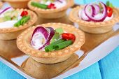 Tartlets with greens and vegetables with sauce on tray on table