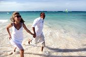 Happy couple running on the beach. Caribbean vacation
