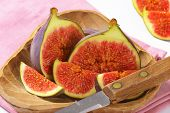 detail of ripe sweet fig, served in the wooden bowl with sharp knife