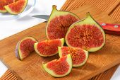 figs portioned with sharp knife and served on the brown wooden cutting board