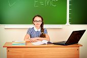 Modern schoolgirl sits at a desk during a lesson. Education.