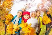 Positive kids with bunch of yellow maple leaves