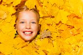 Face of little smiling blond girl in maple leaves