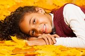 Little African girl lays on autumn yellow leaves