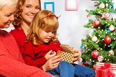 Little girl open presents with mother and granny